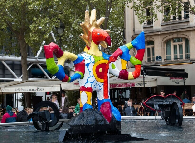 Large colorful rotating statue set in the middle of a large water fountain feature