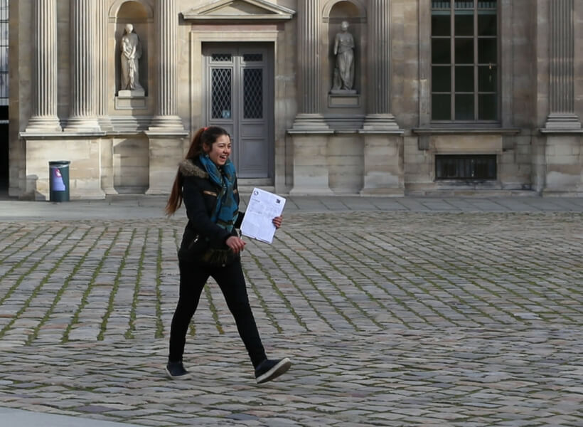 friendly-looking young woman holding a clipboard. She's part of a group of young ladies who try to scam paris visitors every day