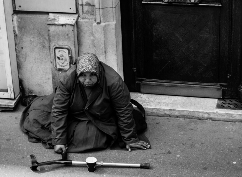 woman begging on the streets of paris, she's wearing a heavy coat and a head covering and has a crutch and paper cup in front of her for donations