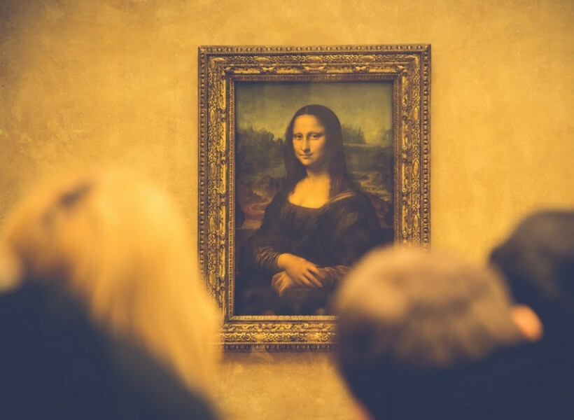 Mona Lisa painting behind glass with several people craning their necks to see her