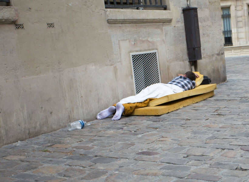 man sleeping on a paris street, he is lying on two foam pads and his face is turned towards the wall