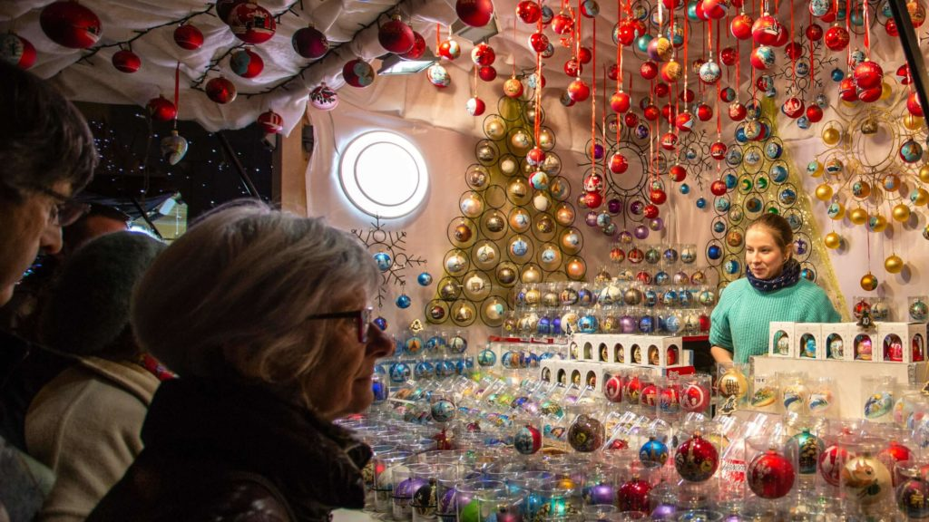 women standing in front of a store that sells christmas decorations at the paris christmas market on the champs elysees