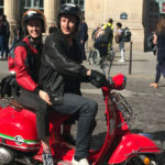 Oliver and his fiancée riding their red scooter in Paris