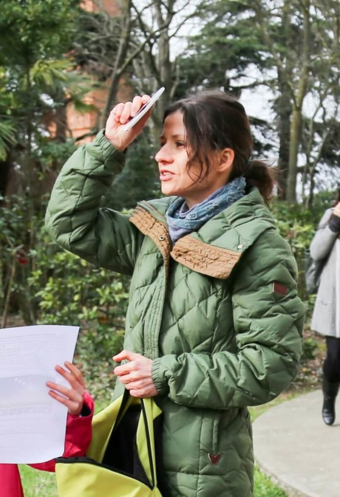 French woman in her 20s wearing a green coat and a blue scarf