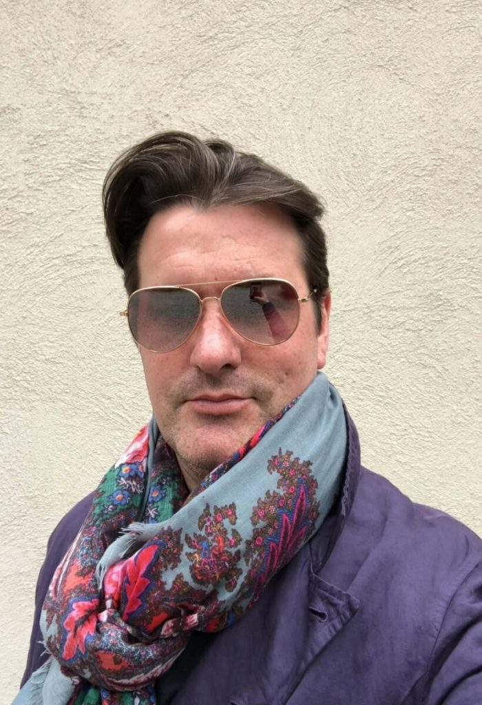 David Palacheck wearing his aviator glasses, his purple sport coat and a colorful scarf