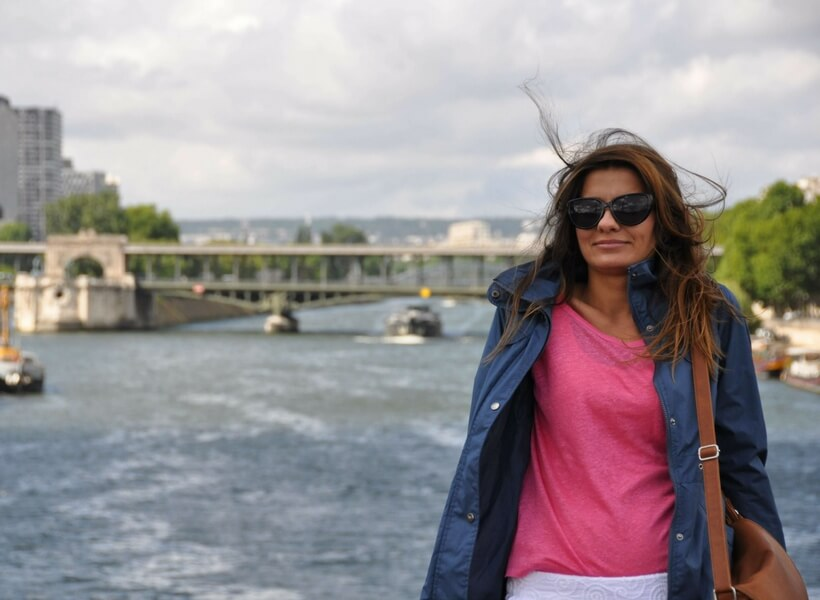 woman wearing a pink t-shirt and a blue wind breaker posing for a photo on a bridge in Paris