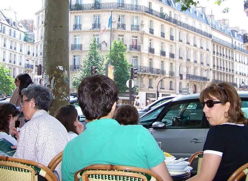 people sitting at a café in Paris with man wearing a bright blue shirt
