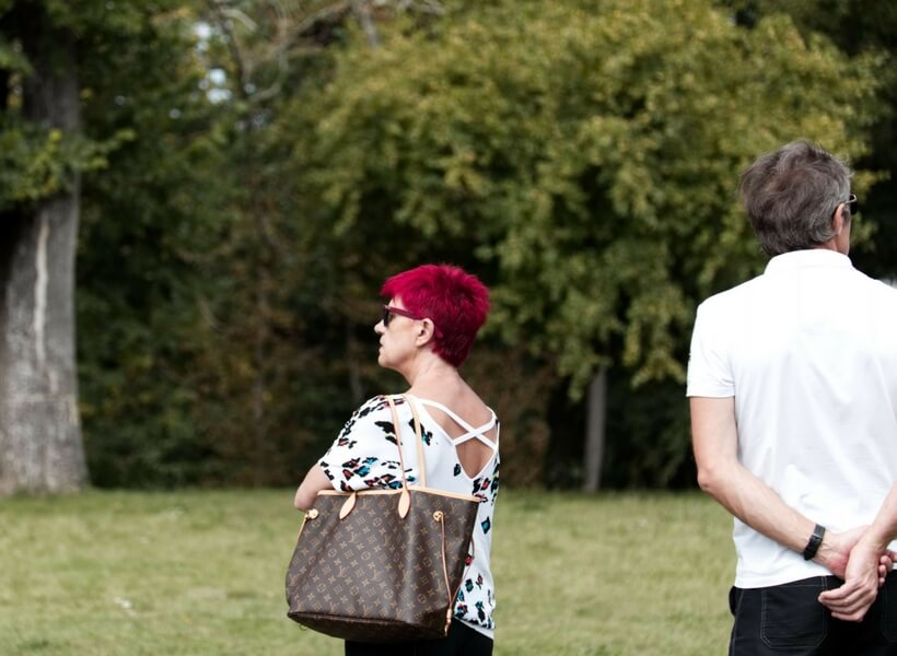 French woman in her early 50s carrying a large fashionable purse and sporting bright burgundy/red hair