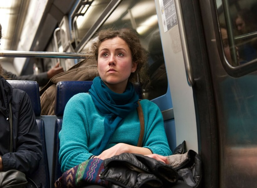 woman in her late 20s wearing a light blue shirt and a dark blue scarf on the metro in paris