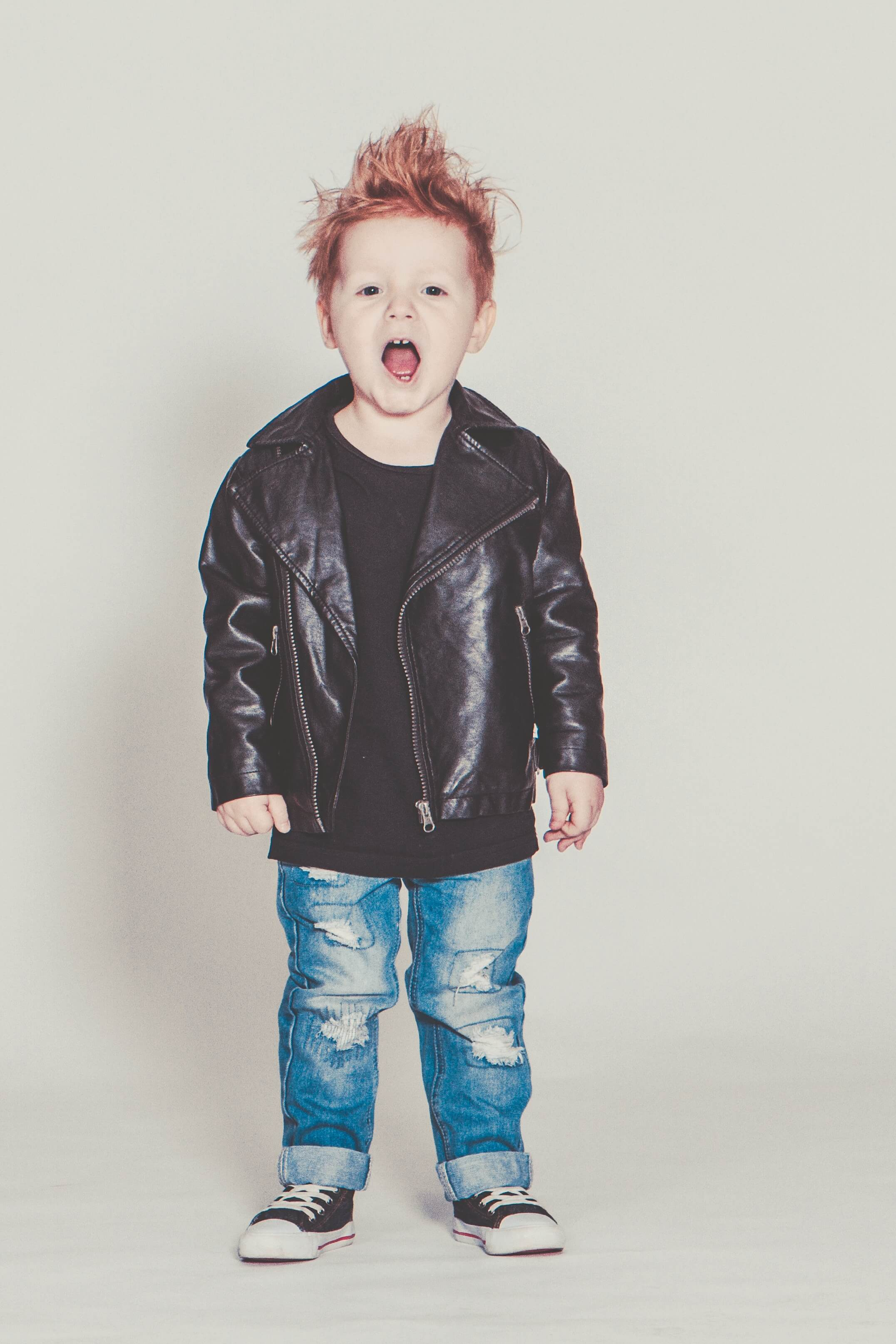 3 year old boy with red hair wearing holey jeans, tennis shoes, a black t-shirt and a perfecto jacket