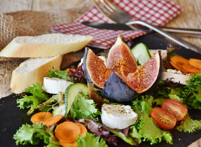 Salad with greens, carrots, avocado, cherry tomatoes, goat cheese and a fig