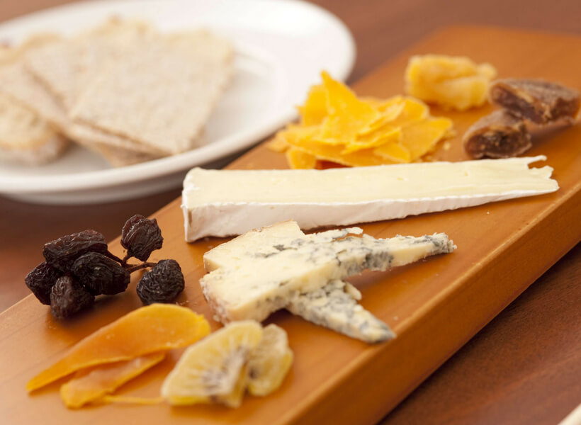 cheese platter with various slivers of cheese and crackers