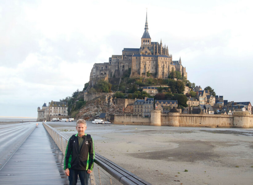 Phil Roberson standing in front of the Mont Saint Michel in Normandy