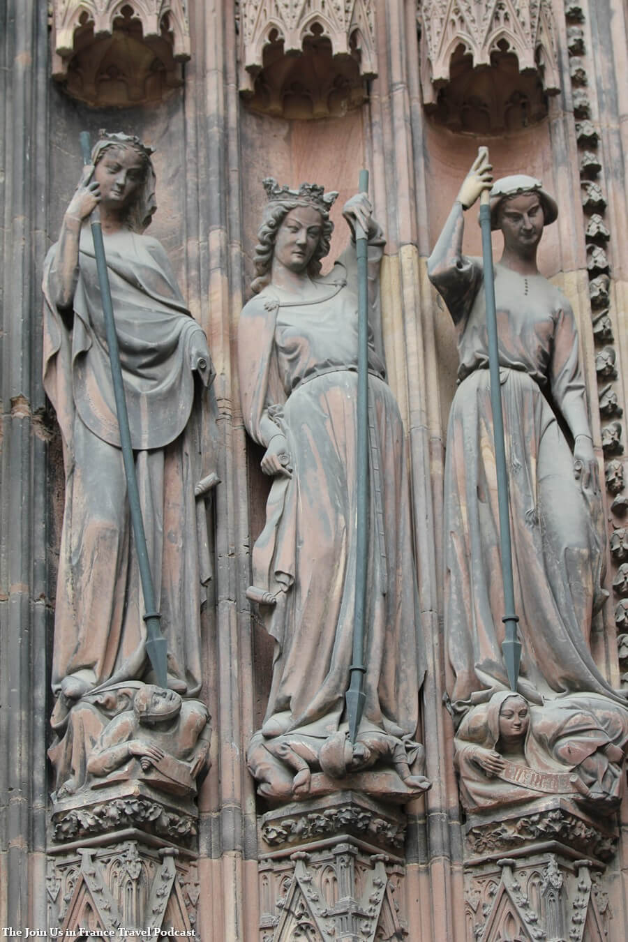 Statue of 3 women carrying spears outside of the Strasbourg Cathedral