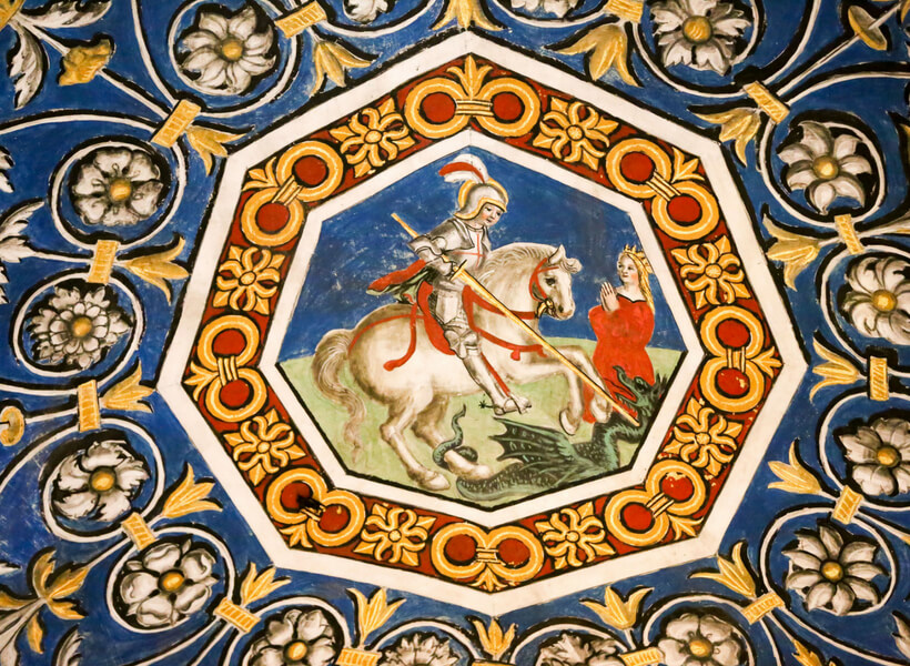 Detail on the cieling of the Albi Cathedral: armored man on a horse kills a dragon while a woman with a crown watches