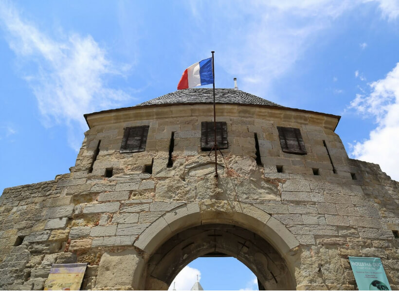 the entrance to the chateau comtal with french flag flying above it