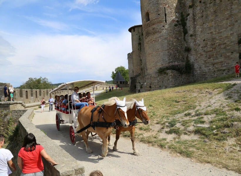 horses and carriage with visitors on board going between the two walls of carcassonne