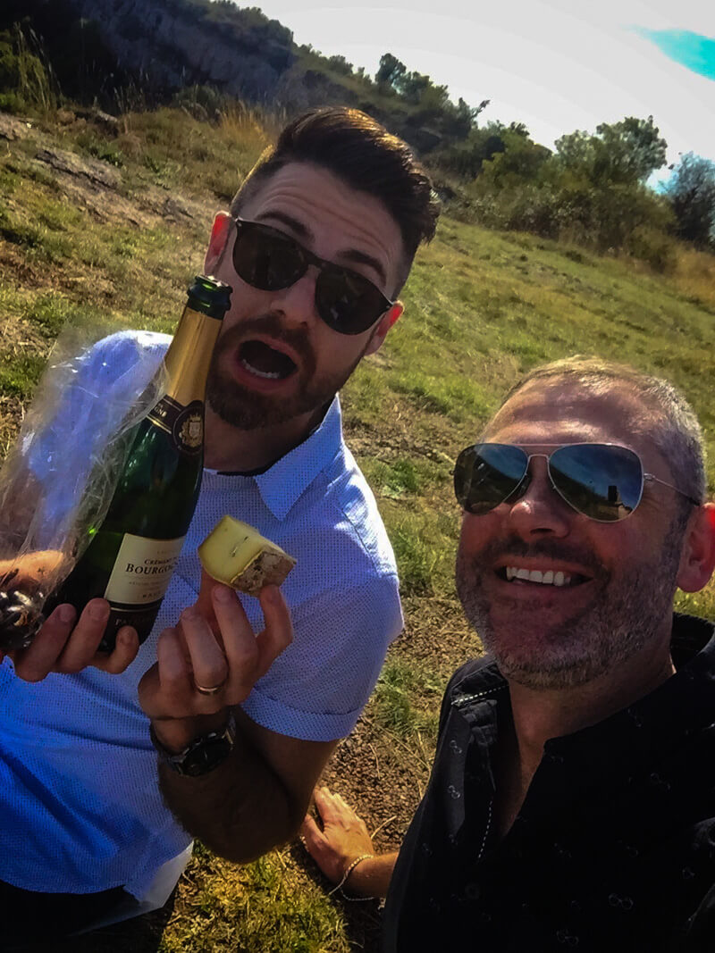 Two men with a bottle of wine and some cheese