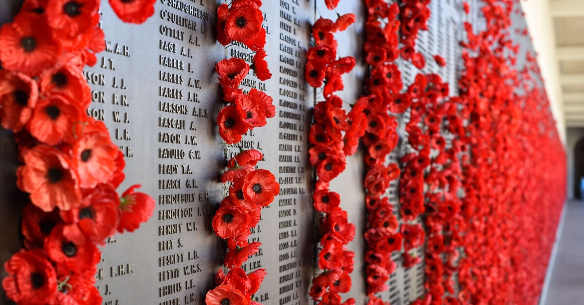 WW1 memorial site covered in garlands of red flowers