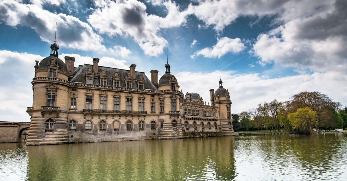 Chateau of Chantilly surrounded by water with a dramatic blue sky and white clouds