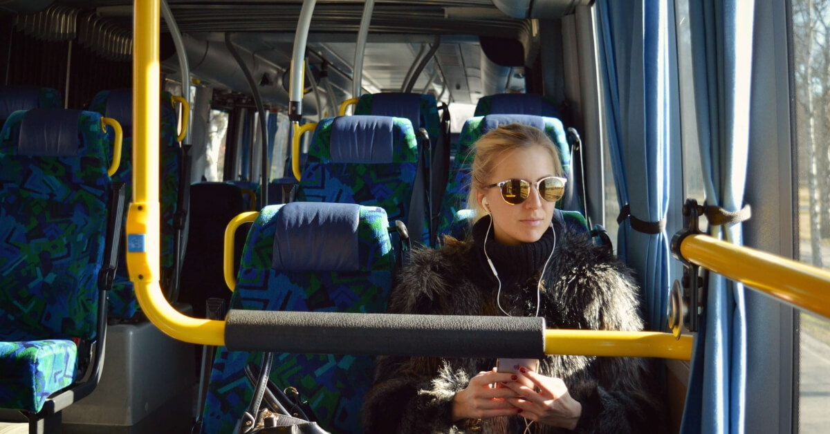 woman on a bus listening to a podcast during her commute to work