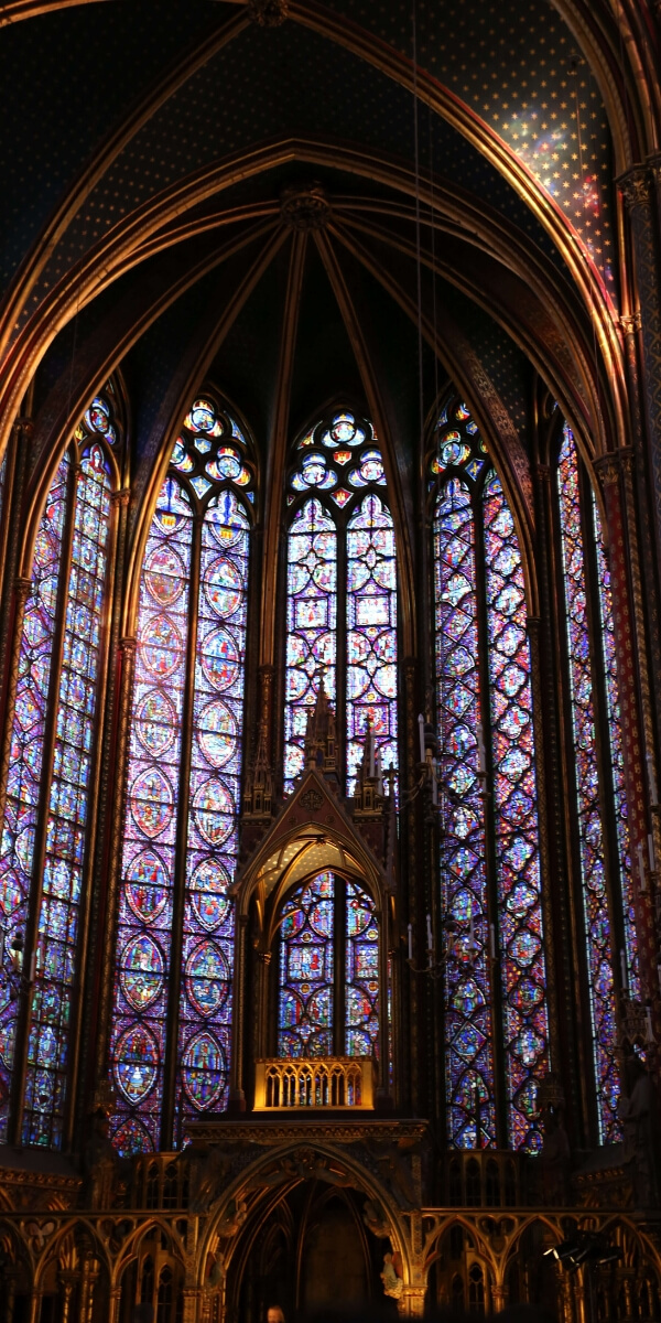 several panels of stained-glass windows at the Sainte Chapelle in Paris including beautiful light reflections on the stone