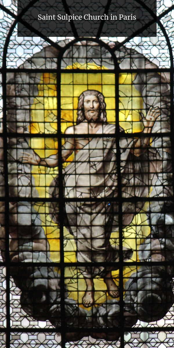 renaissance stained-glass with a large Jesus surrounded by yellow glass at Saint-Sulpice church in Paris