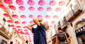 Jessica's son looking up at umbrellas lining a street in France and taking a picture. Great Activities in France for Families with Children episode.