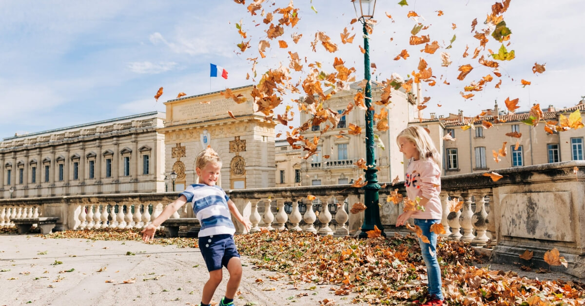 Boy and girl playing with dead leaves in the Tuileries garden: vacation photos episode