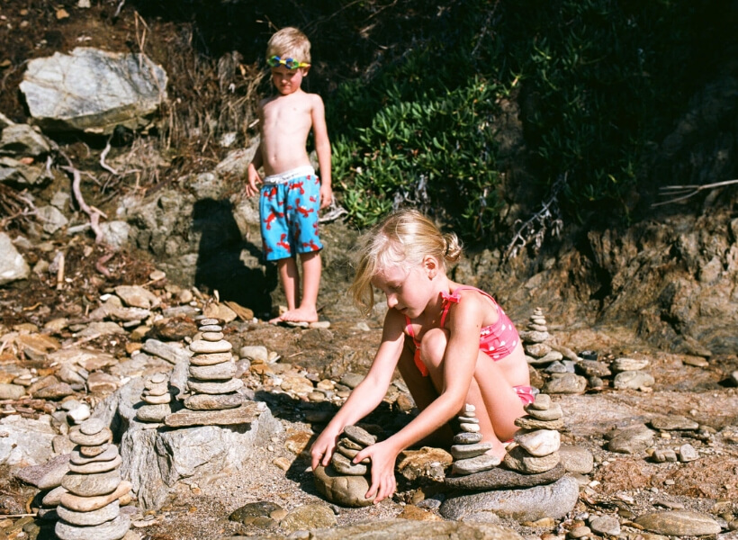 Children playing with rocks along a river bed: Great Destinations in France for Families