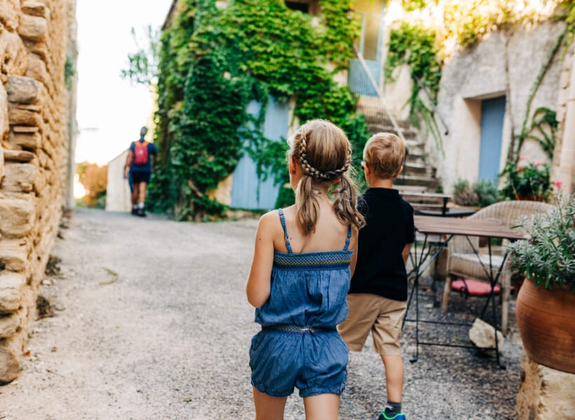we see the back of a boy and a girl walking in a scenic street in France: vacation photos episode