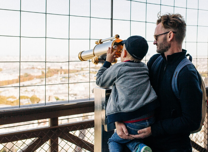 Father holding his son while the son looks through binoculars on the Eiffel Tower: Great Destinations in France for Families Episode