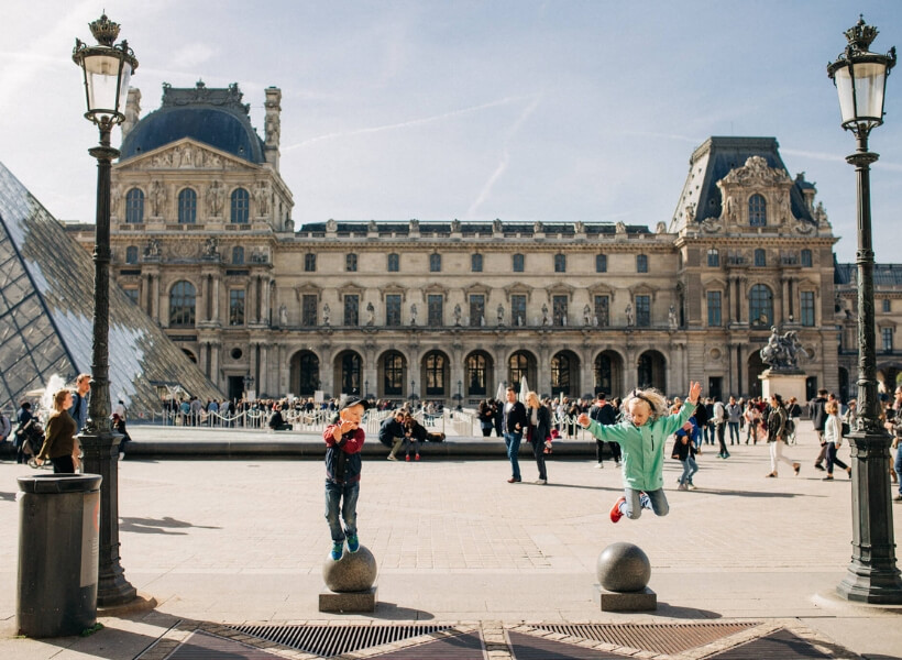 children jumping up and having a good time in front of the Louvre Museum: Great Destinations in France for Families episode