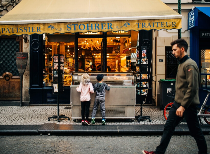 boy and girl carefully examining the ice cream flavors at their disposal on a Paris street: vacation photos