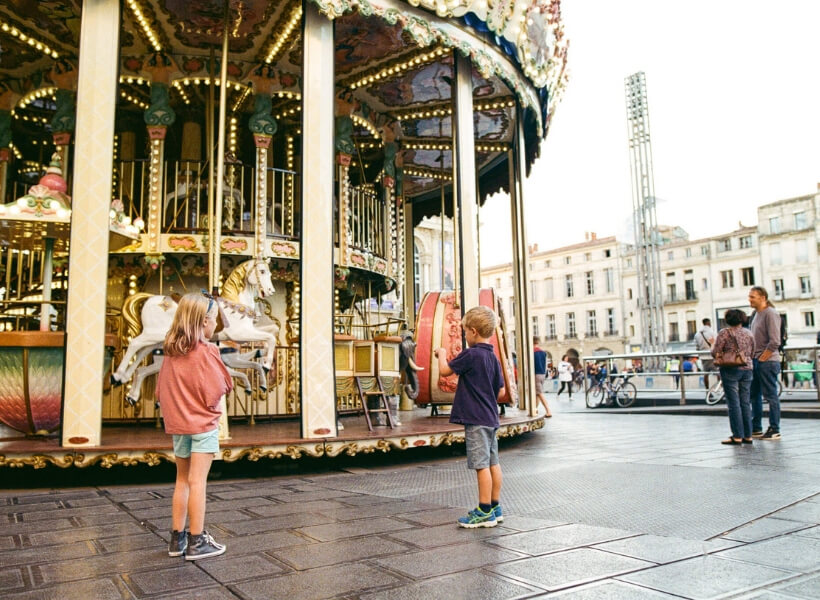 children looking at a carrousel in Montpellier: Great Destinations in France for Families episode