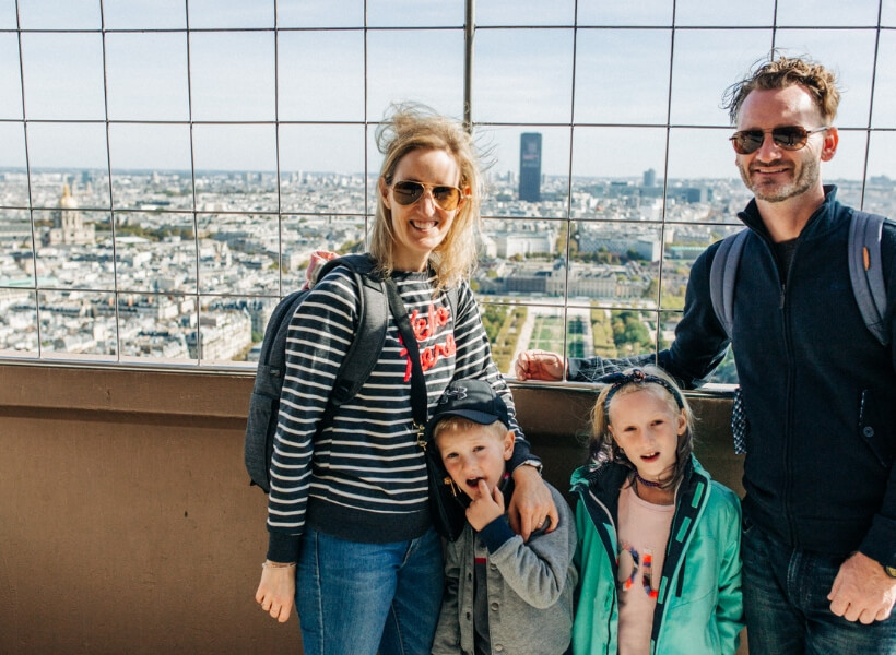 Jessica and her family posing on top of the Eiffel Tower: vacation photos