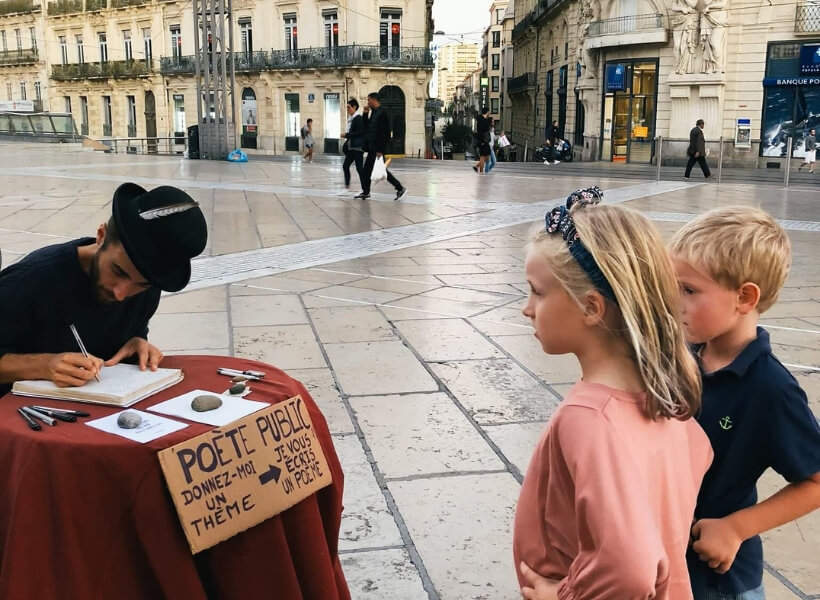 children talking to a street poet who is writing them a poem as they watch: Great Destinations in France for Families episode