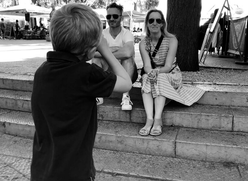 Boy taking a photo of his parents who are sitting on some stairs: Great Destinations in France for Families Episode