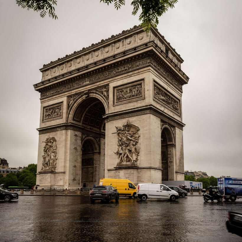 Arc de Triomphe with cars driving in front of it and wet pavement. 4 days in Paris episode.