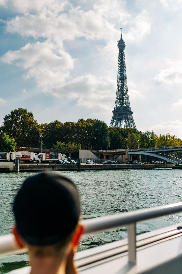 Boy looking at the Eiffel Tower from a boat on the Seine: Great Destinations in France for Families Episode