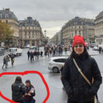 Eric's wife posing in front of the Paris Opera with scammers working in the background