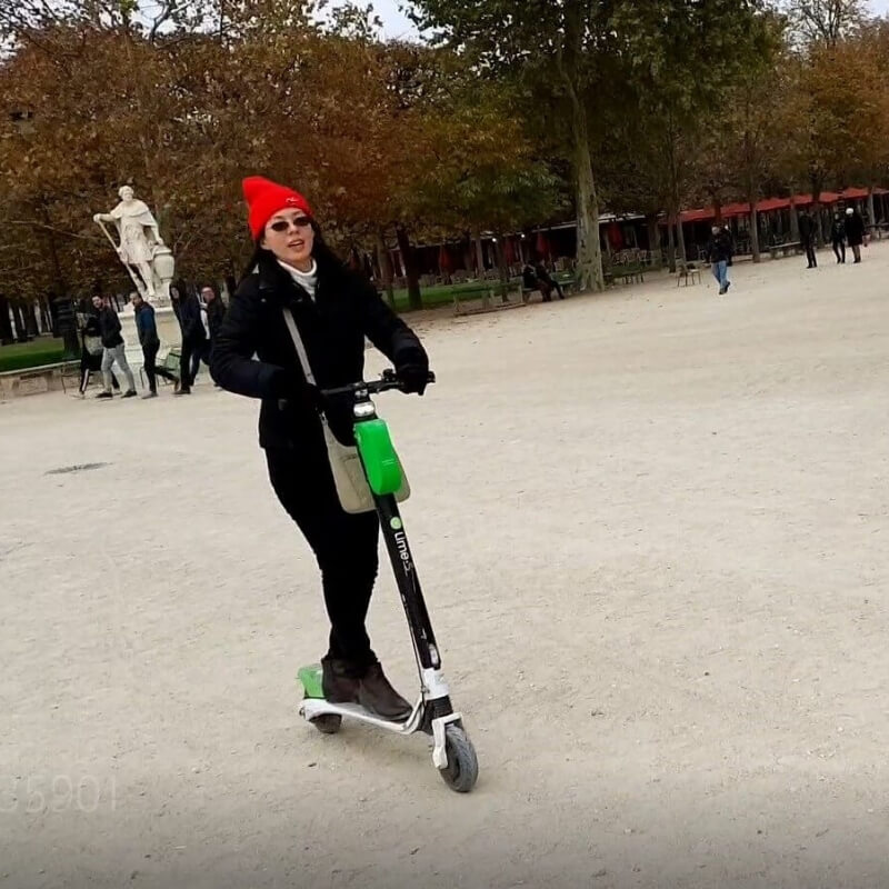 Eric's wife riding a scooter inside the Luxembourg Gardens