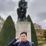 Eric posing in front of Rodin Thinker looking like he's in deep thought