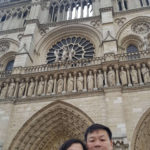 Eric and his wife posing in front of Notre Dame Cathedral
