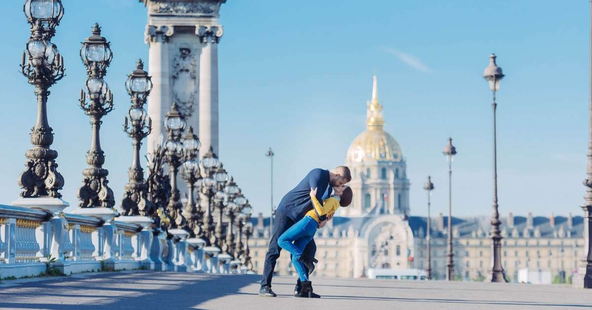 Emily and her husband kissing on the Alexander III bridge