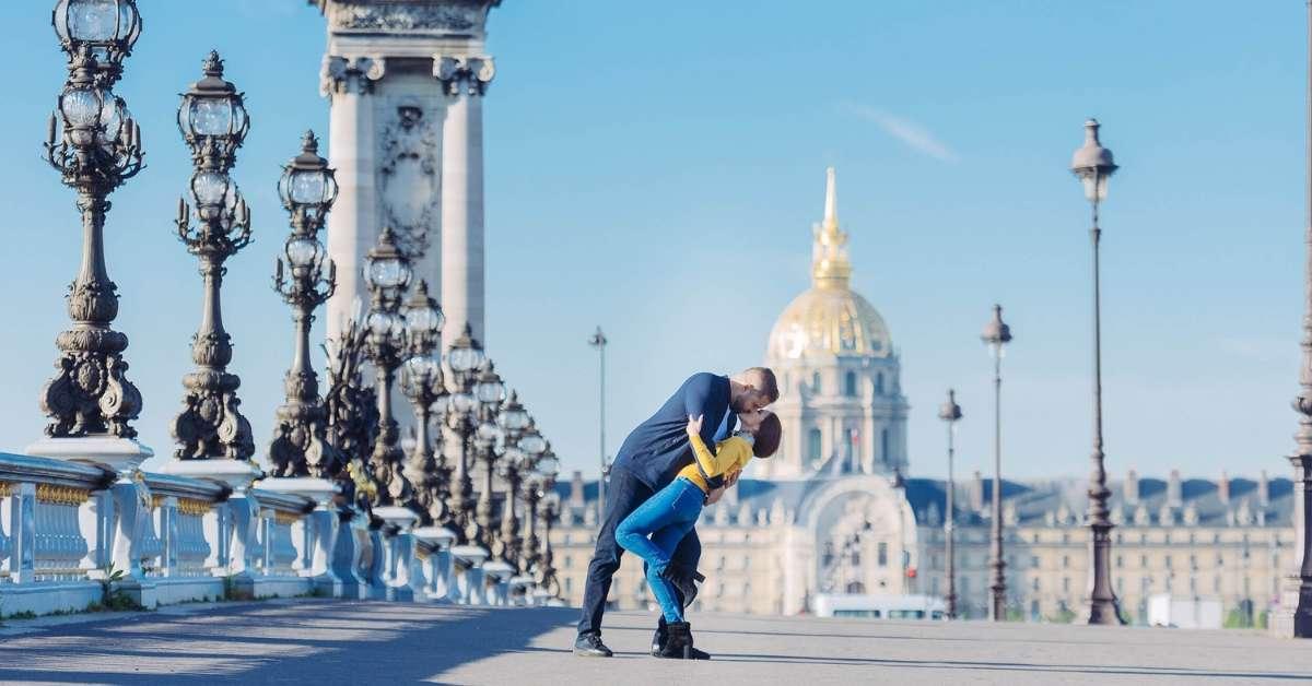 Emily and her husband kissing on the Alexander III bridge