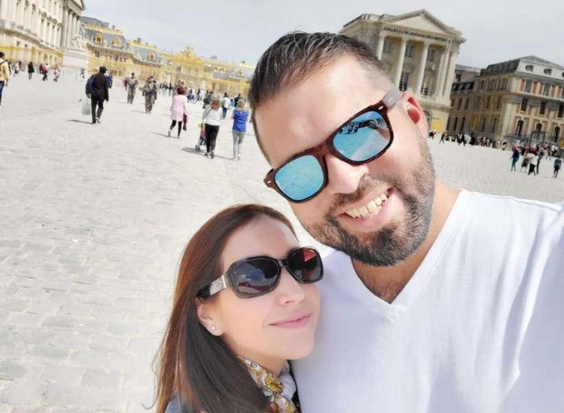Emily and her husband doing a selfie in front of Versailles while on their honeymoon in Paris