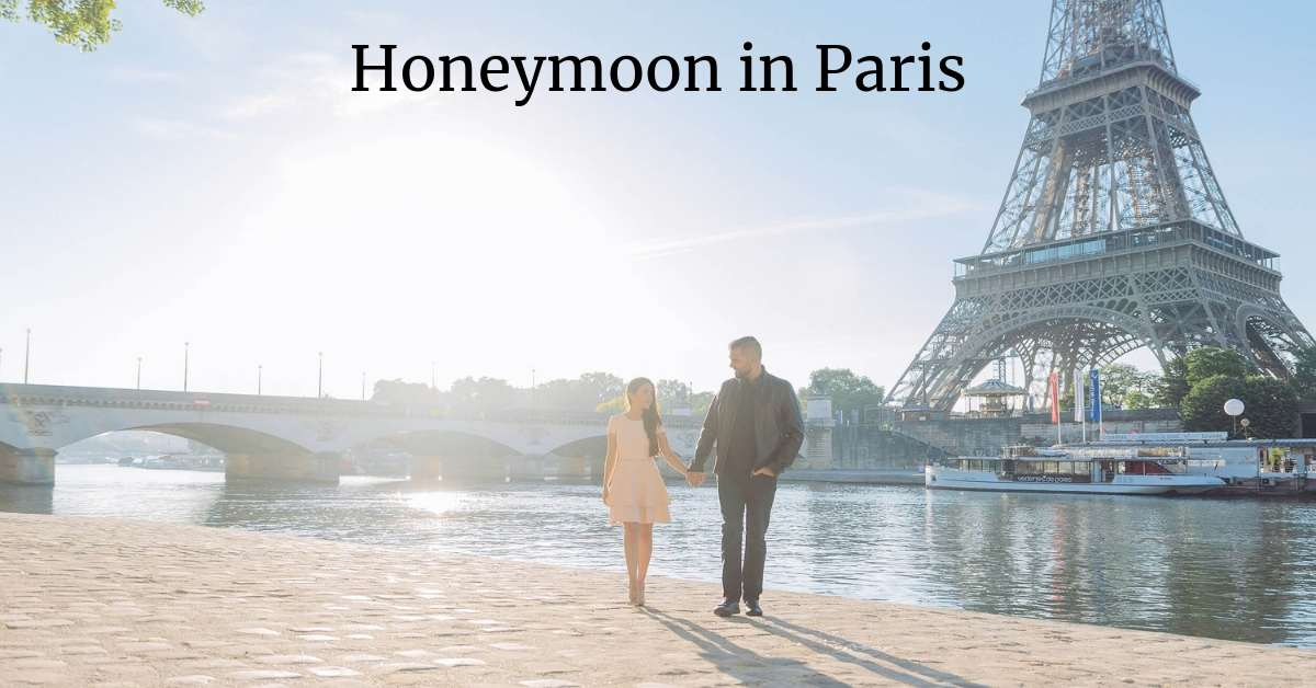 Couple walking along the Seime River with the Eiffel Tower in the background: honeymoon in Paris episode