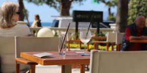 Seaside café with empty glasses on a table and the sea in the background