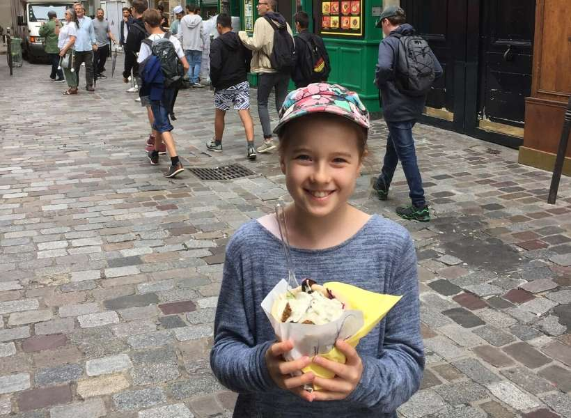 Joanne's daughter holding her fallafel sandwich from As du Fallafel in the Marais